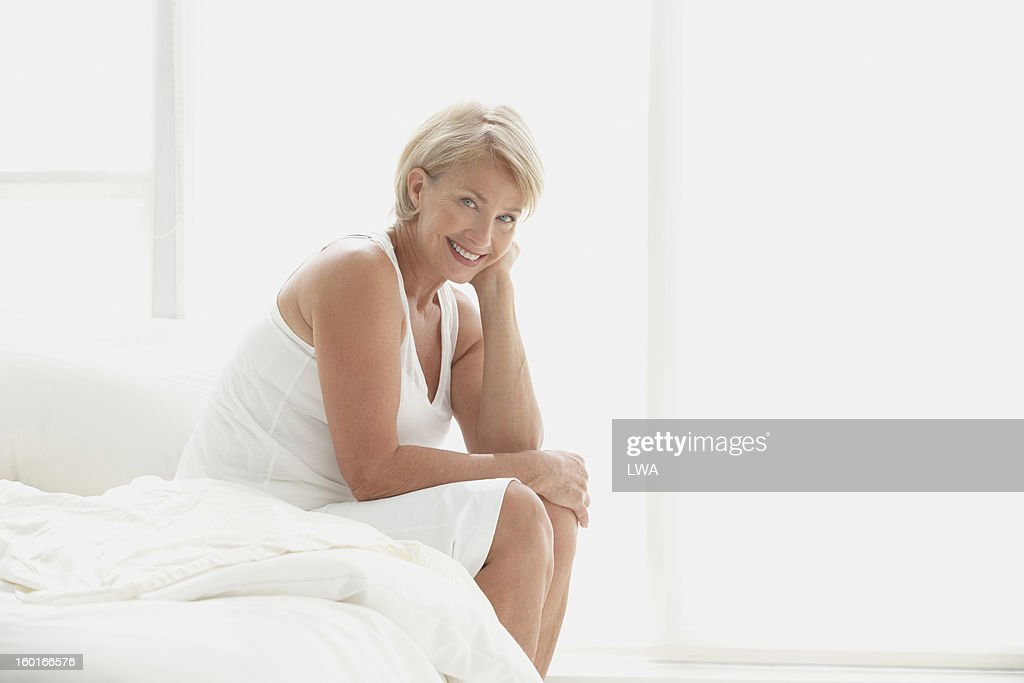 Smiling mature woman sitting on bed