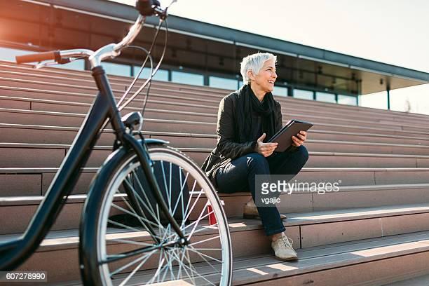 Sonriendo de edad mujer usando tableta Digital al aire libre.