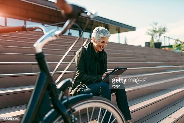 Sonriendo de edad mujer usando tableta Digital.