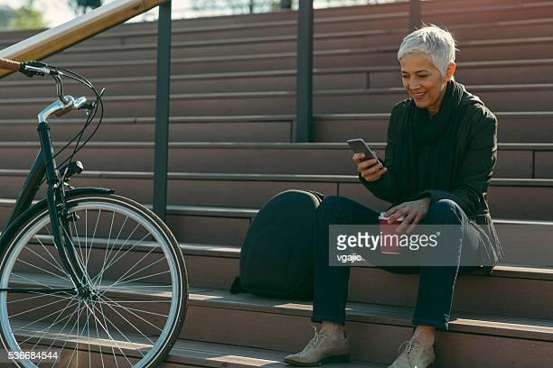 Sonriendo de edad mujer usando teléfono inteligente.