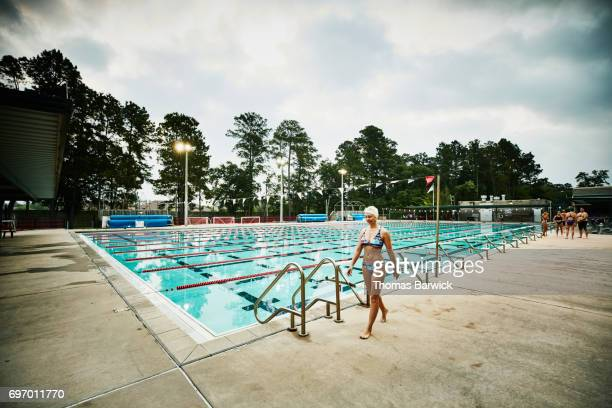 Smiling mature woman walking on outdoor pool deck before starting early morning workout