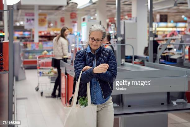 Smiling mature woman walking with shopping bag at supermarket