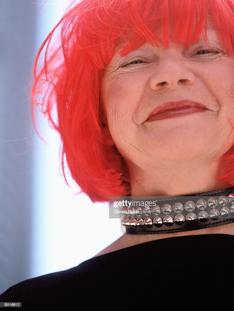 Smiling mature woman wearing red wig and studded collar, portrait