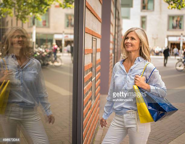Smiling mature woman with grey hair window shopping in town
