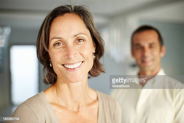 Smiling, mature woman with her husband in the background