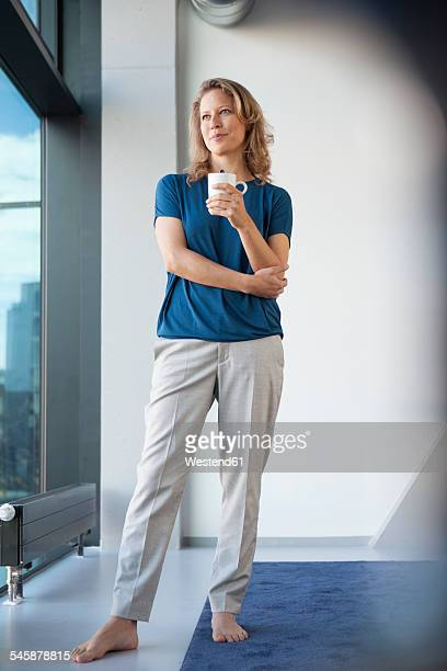 Smiling mature woman with mug looking through window at her apartment
