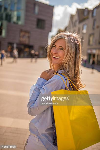 Smiling mature woman with shopping bags looking back at you