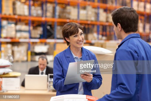 Smiling mature woman writing on clipboard : Stock Photo