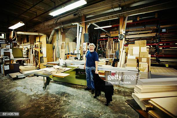 Smiling mature woodworker with dog in woodshop