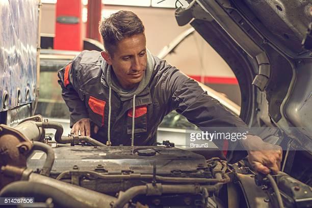 Sonriendo mecánico arreglando un motor de camión en Automático reparación.