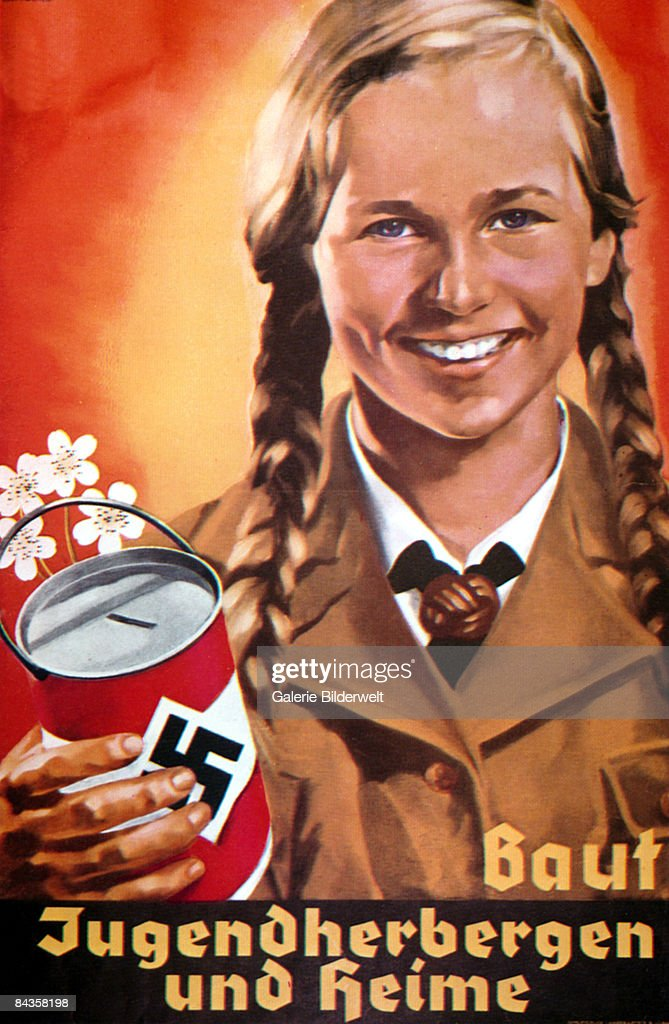 A smiling member of the BDM (Bund Deutscher Madel), the female branch of the Hitler Youth, carrying a collecting tin, circa 1938. The caption reads 'Baut Jugendherbergen und Heime' ('Build youth hostels and homes'. Poster by Hermann Witte.