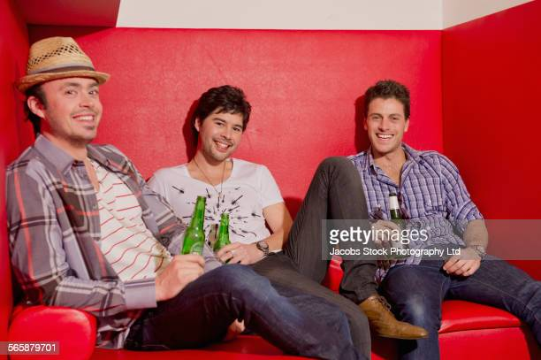 Smiling men drinking and relaxing in lounge