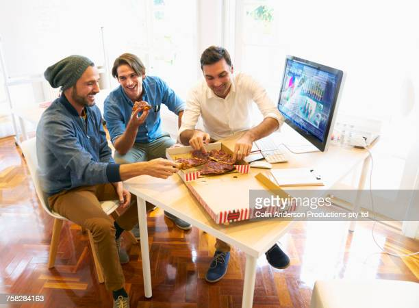 Smiling men eating pizza in office