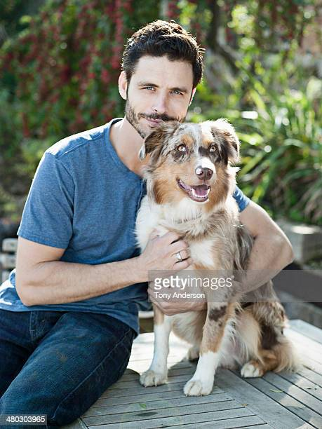 Smiling men holding his dog in backyard garden