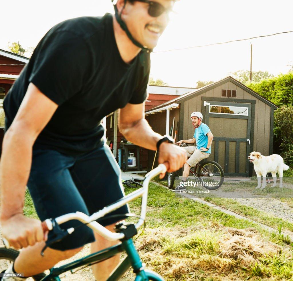 Smiling men riding BMX bikes on backyard dirt track on summer evening : Stock Photo