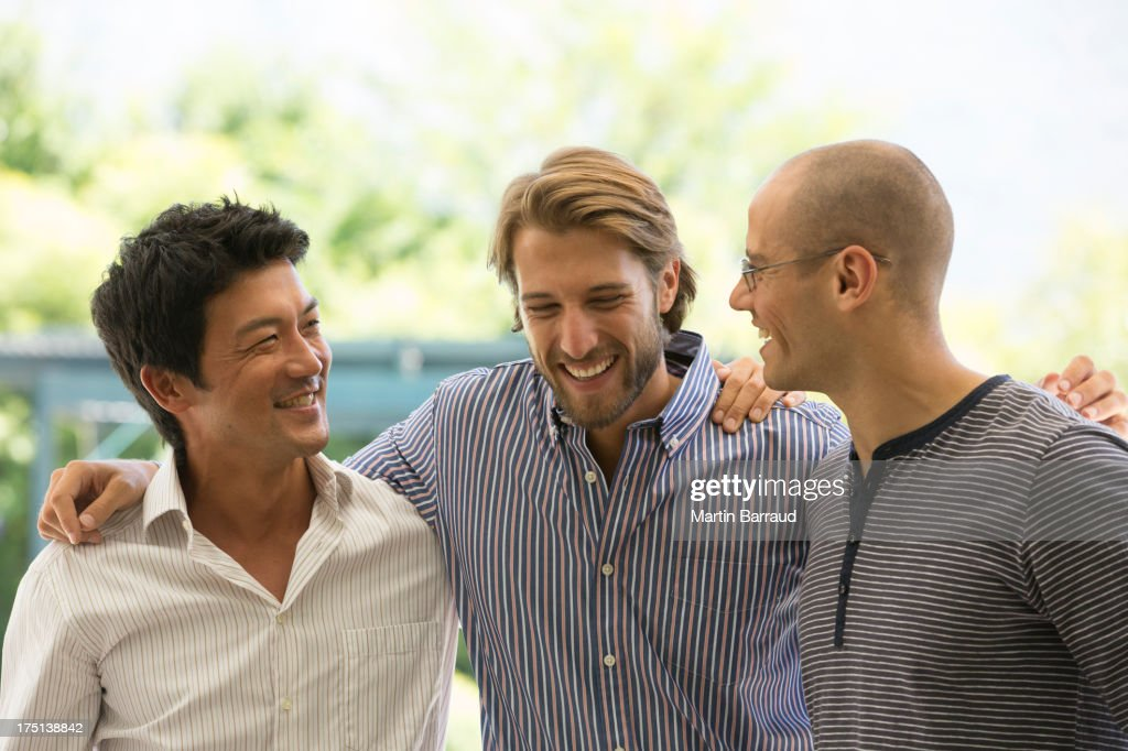 Smiling men talking outdoors : Stock Photo
