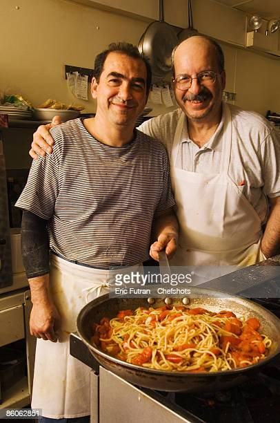 Smiling men with pan of pasta and tomatoes