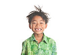 This adorable 7 year old flashes a bright smile for the camera, revealing two front missing teeth.  Wearing a green Hawaiian shirt, this child encompasses the Spirit of Aloha through his happy and pos