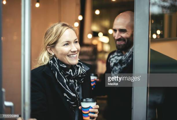 Smiling mid adult businesswoman and businessman leaving cafe
