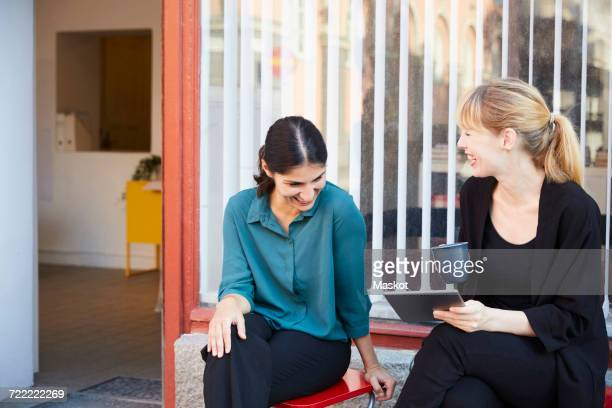 Smiling mid adult businesswomen sitting outside office