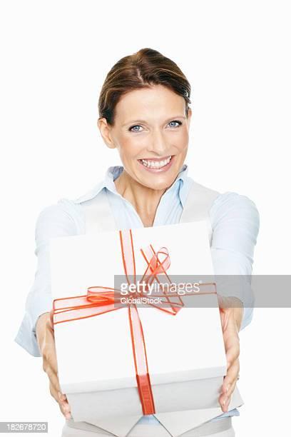 Souriant milieu adulte femme tenant la boîte-cadeau