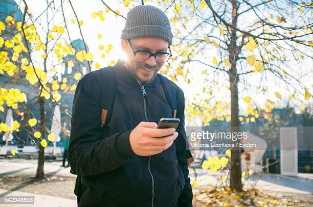 Smiling Mid Adult Man Using Phone On Footpath