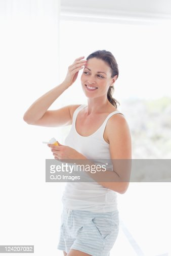 Smiling mid adult woman applying face cream : Stock Photo