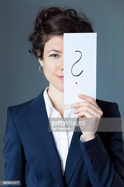 Smiling mid adult woman holding paper with question mark, close-up