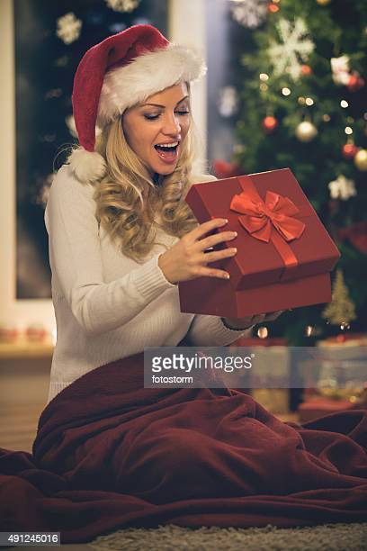 Smiling mid adult woman opening Christmas present