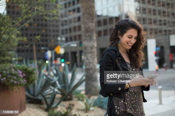 Smiling mid adult woman using mobile phone against buildings in city, Los Angeles, California, USA