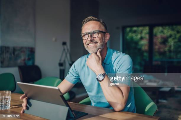smiling midaged man with glasses at table with tablet