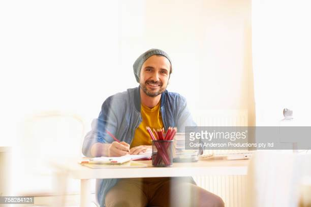 Smiling Middle Eastern man writing in office