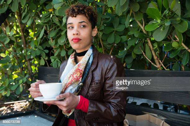 Smiling Millennial Mixed Race Woman Enjoying Coffee Outdoors in Miami