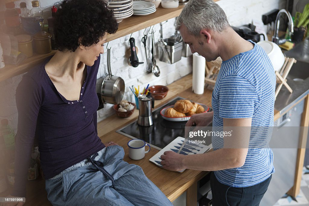 A smiling mixed age couple preparing food in their kitchen : Stock Photo