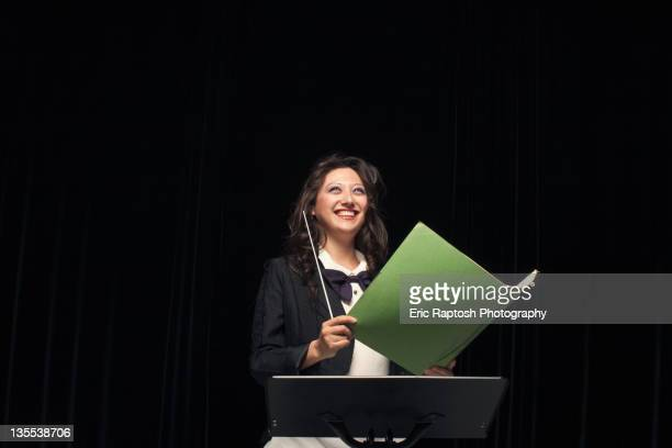 Smiling mixed race conductor holding folder