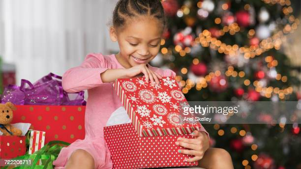 Smiling Mixed Race girl opening gift box on Christmas
