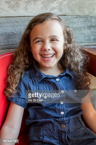 Smiling mixed race girl sitting in chair : Stock Photo