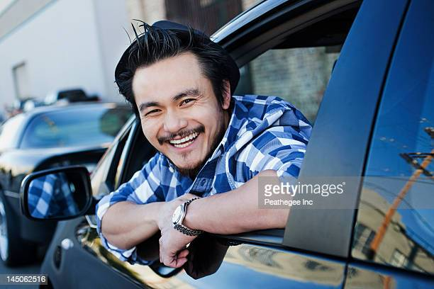 Smiling mixed race man in compact car