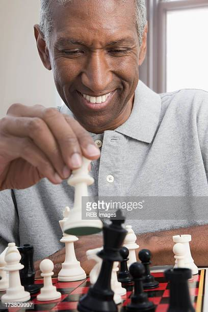 Smiling mixed race man playing chess