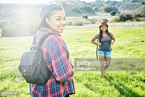 Smiling Mixed Race sisters backpacking in field near mountain