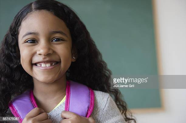 Smiling mixed race student wearing backpack in classroom