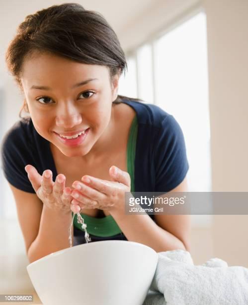 Smiling mixed race teenage girl washing face