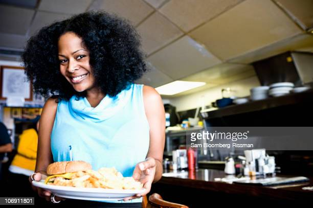 Smiling mixed race waitress holding plate of food in diner