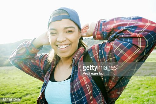 Smiling Mixed Race woman backpacking in field