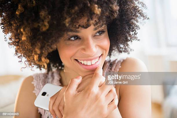 Smiling mixed race woman holding cell phone