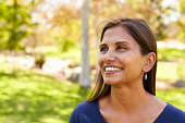Smiling mixed race woman in park looking away from camera
