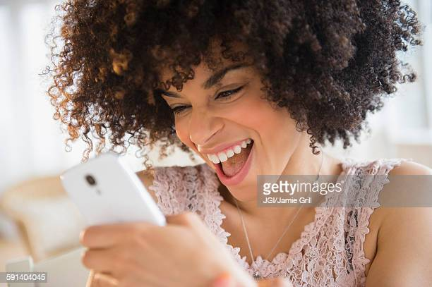 Smiling mixed race woman using cell phone