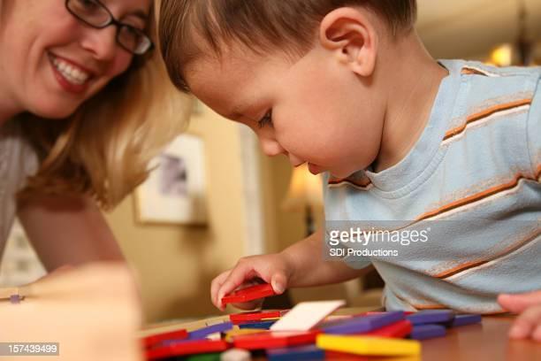 Smiling Mom Helping Toddler Playing With Blocks