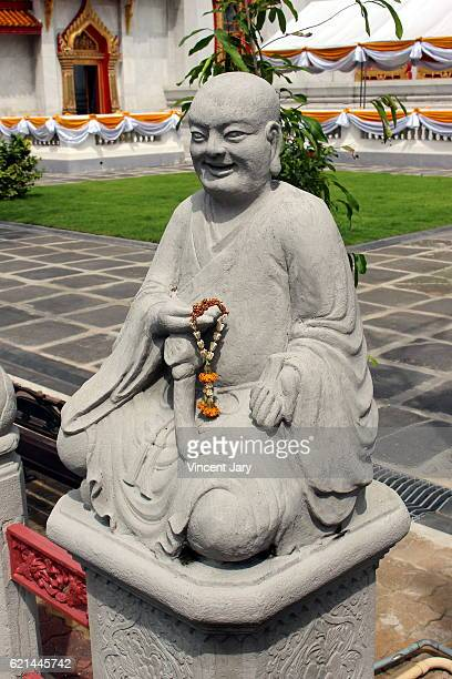 Smiling monk statue Wat Benchamabophit temple Bangkok Thailand