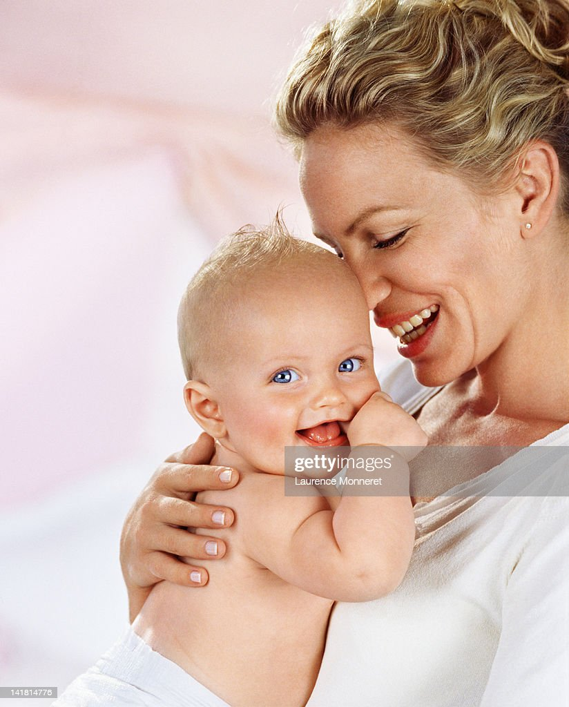 Smiling mother and baby hugging together